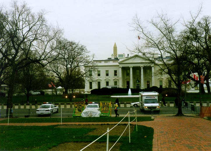 White House with an armed man on its roof seen right to Washington Monument. Washington DC