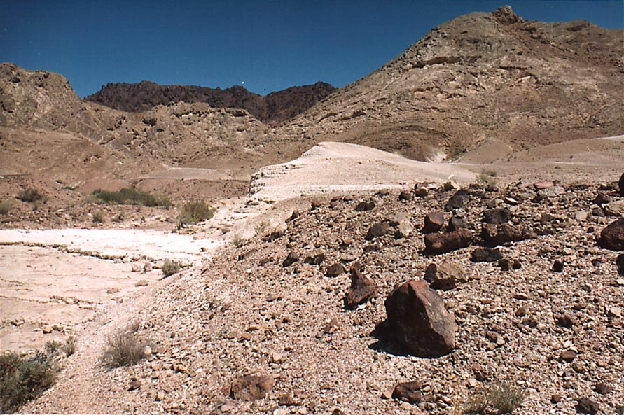 A wadi approaching Ramon's Tooth (black hill...from Mitzpe Ramon. The Middle East