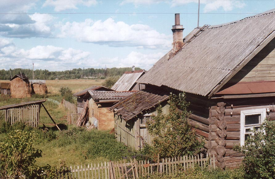 A wooden cabin north from Novgorod, view from a bus. Russia