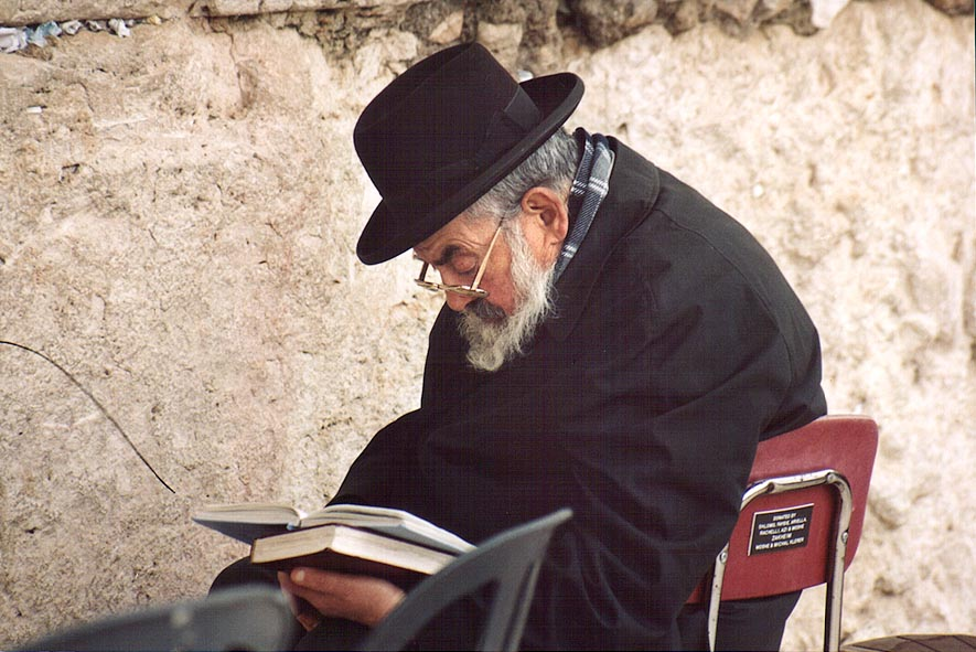 A prayer sitting in front of Western, or Wailing Wall. Jerusalem, the Middle East