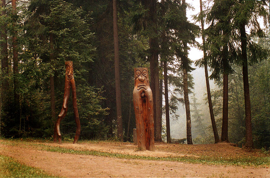 Wooden sculptures in Kavgolovskiy Park near...with smoke is from burning forests