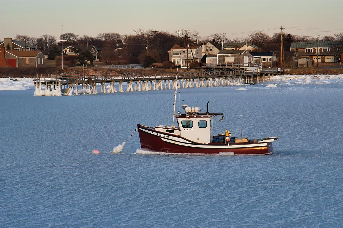 "A fishing boat ""Happy Hunter"" in a frozen Sakonnet Harbor. Rhode Island"