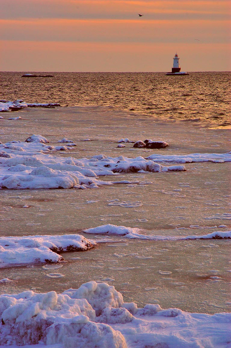Icy ocean and Sakonnet Lighthouse at sunset, view from Breakwater Point. Rhode Island