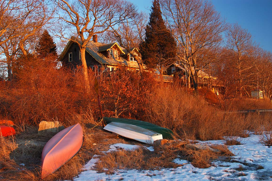 A village and boats on the bank of frozen Slocums...at sunset. Dartmouth, Massachusetts