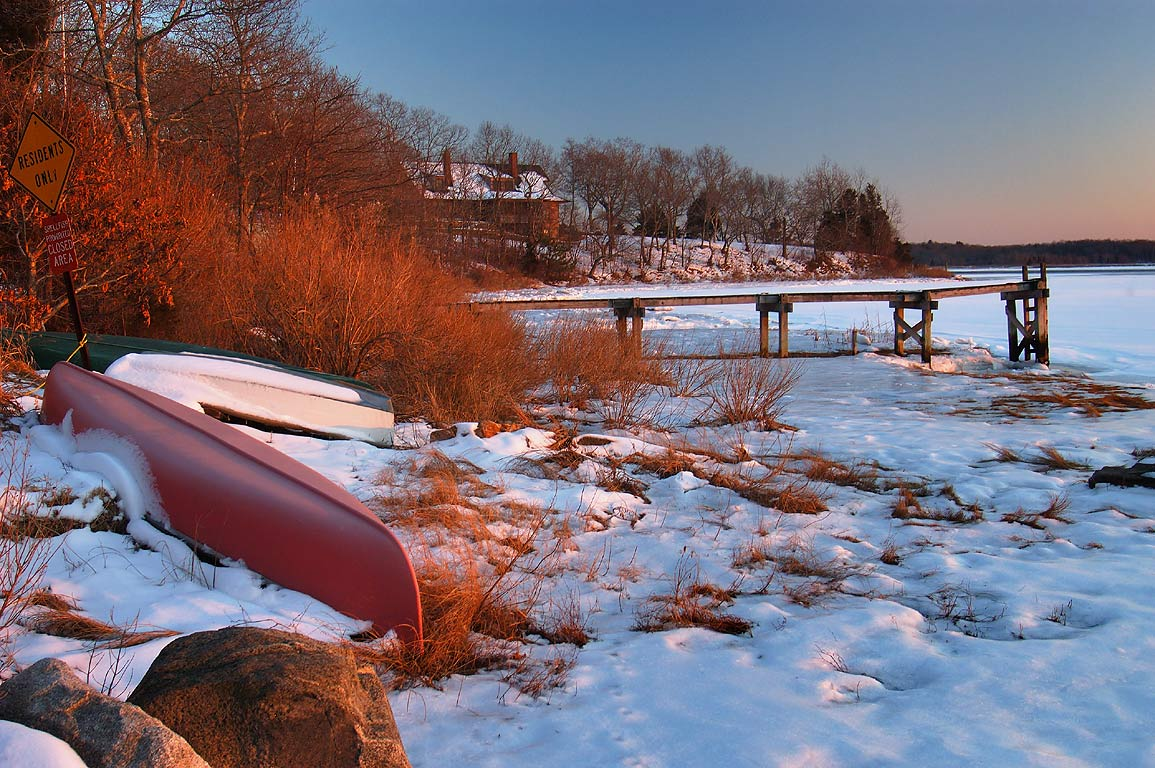 Boats and frozen Slocum's River at the end of...at sunset. Dartmouth, Massachusetts