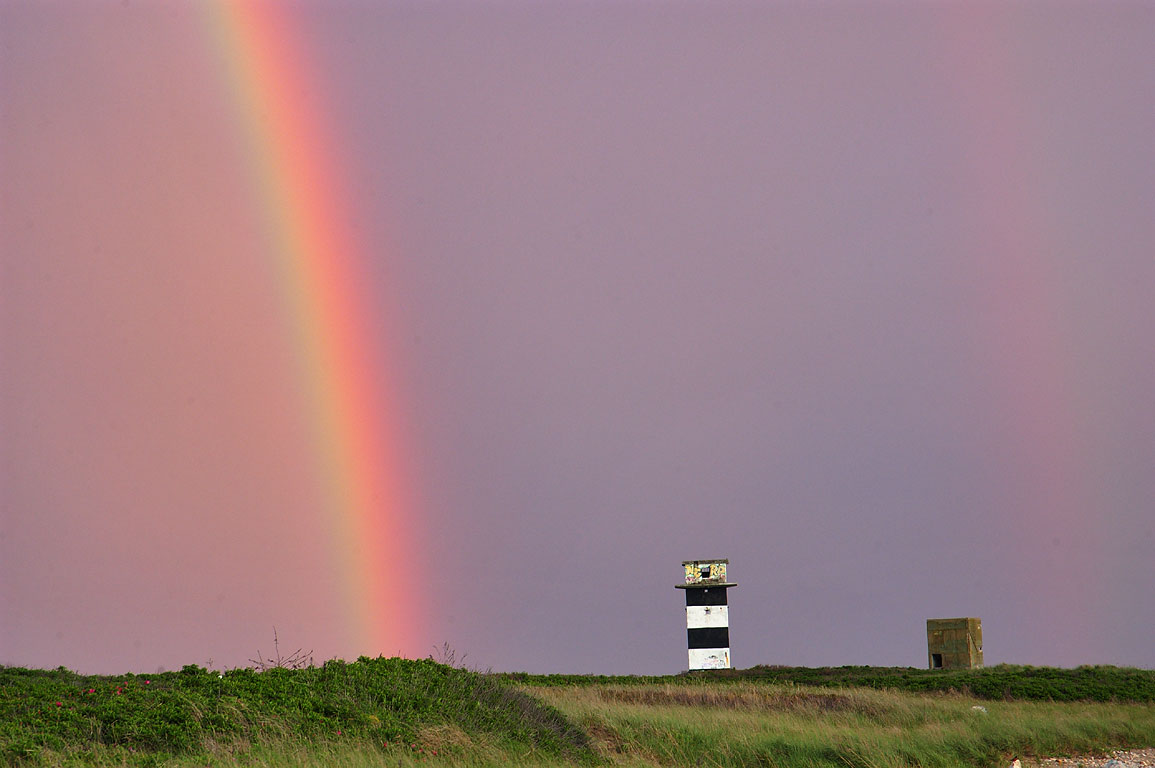 A rainbow and artillery fire control towers on Gooseberry Neck. Westport, Massachusetts