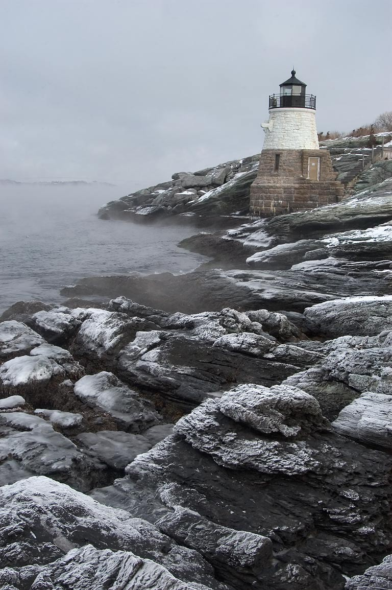 Castle Hill Lighthouse, with condensed frozen sea...fog on rocks. Newport, Rhode Island