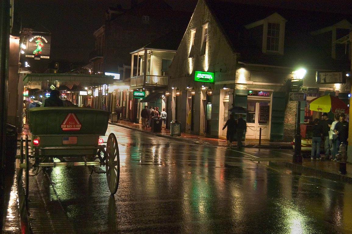 Bourbon Street at rainy evening, with a carriage. New Orleans, Louisiana