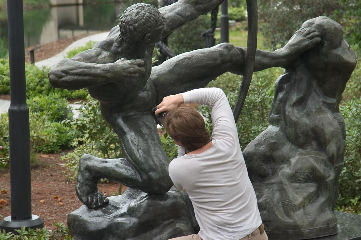 A tourist photographing an outdoor sculpture of NOMA. New Orleans, Louisiana