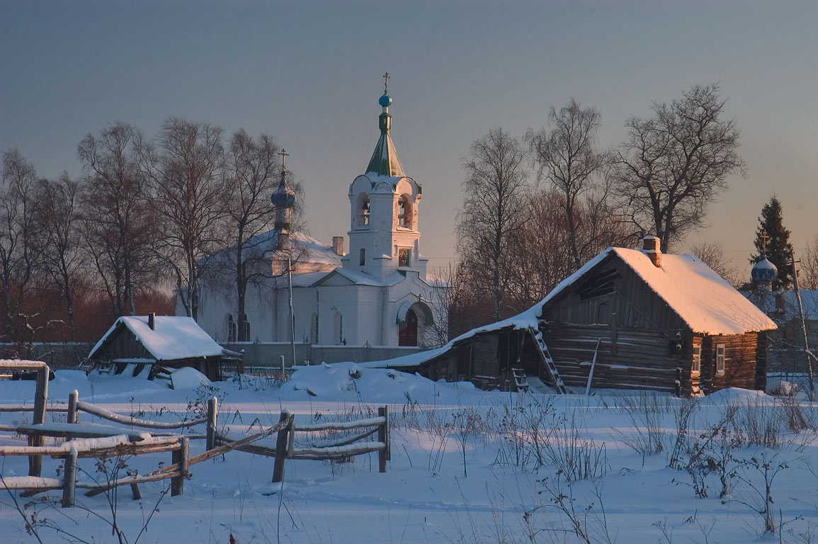 A log house and a church of Spaso-Troitsky Skit...near Tikhvin, Leningrad Region. Russia