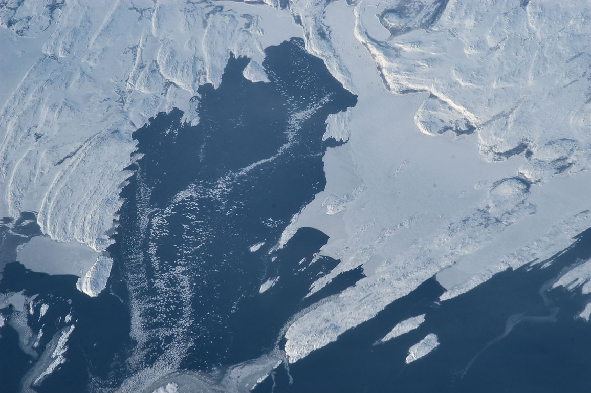 Half-frozen harbor with floating ice in south...from a plane from London to Boston