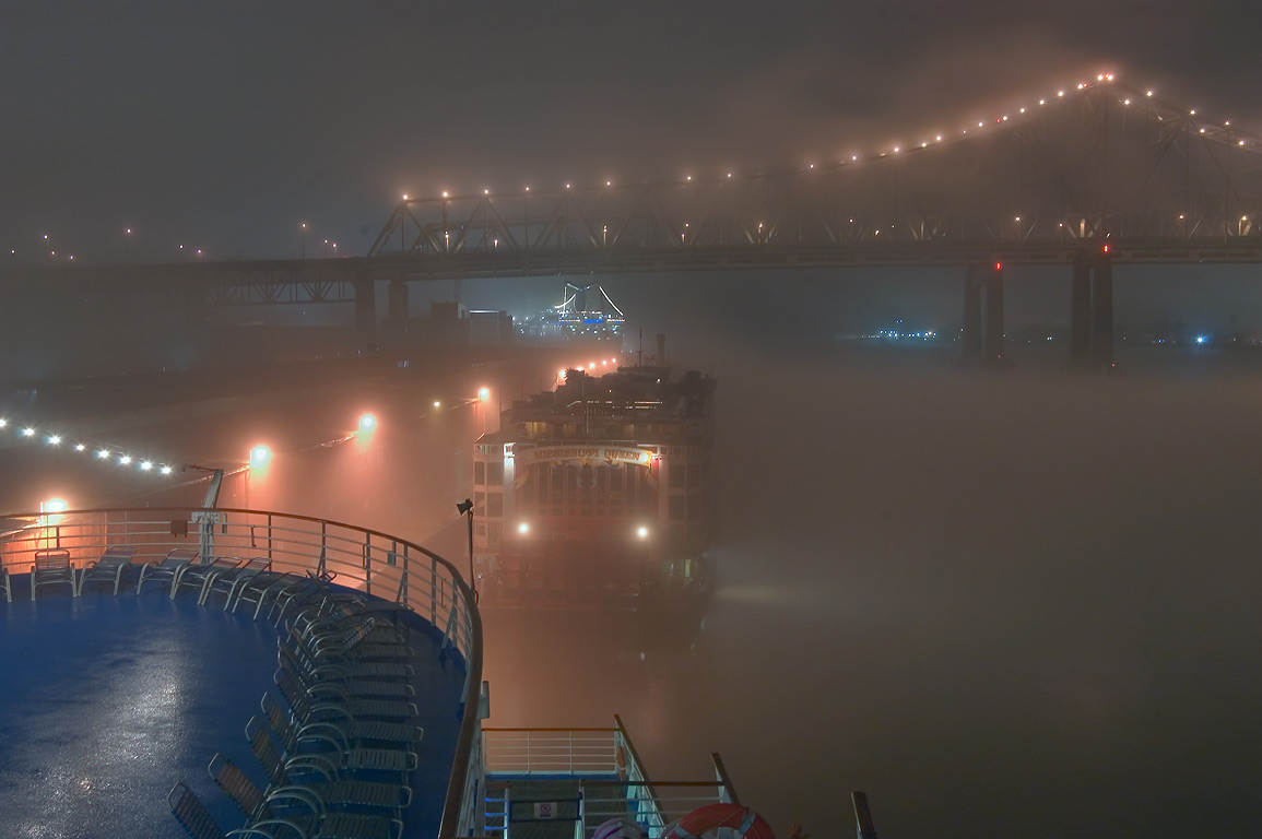 A bridge, Mississippi River, and Robin St. wharf...fog at night. New Orleans, Louisiana