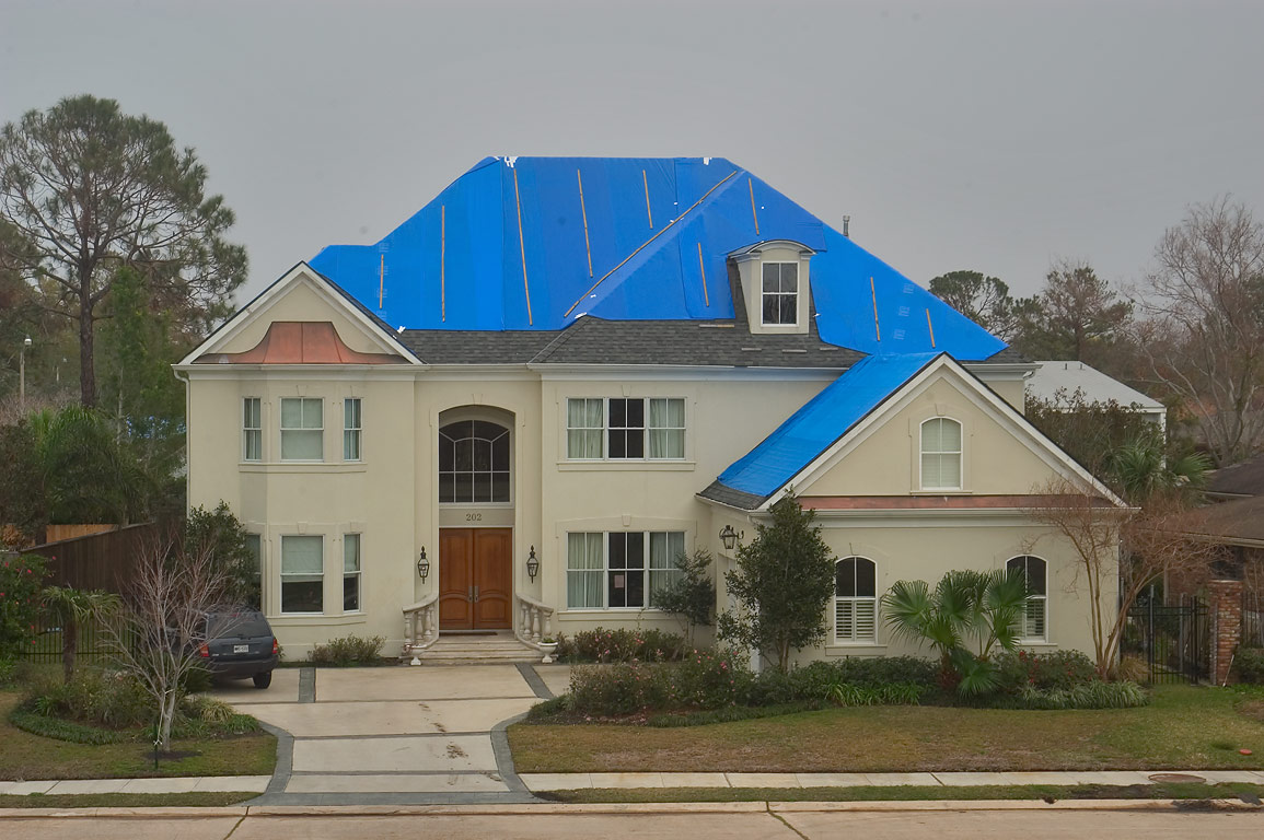 A roof wrapped in bright blue tarp at Lakeshore...from a levee. New Orleans, Louisiana