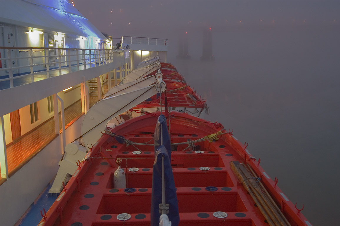 Lifeboats and the city bridge in fog, view from a...St. Wharf. New Orleans, Louisiana