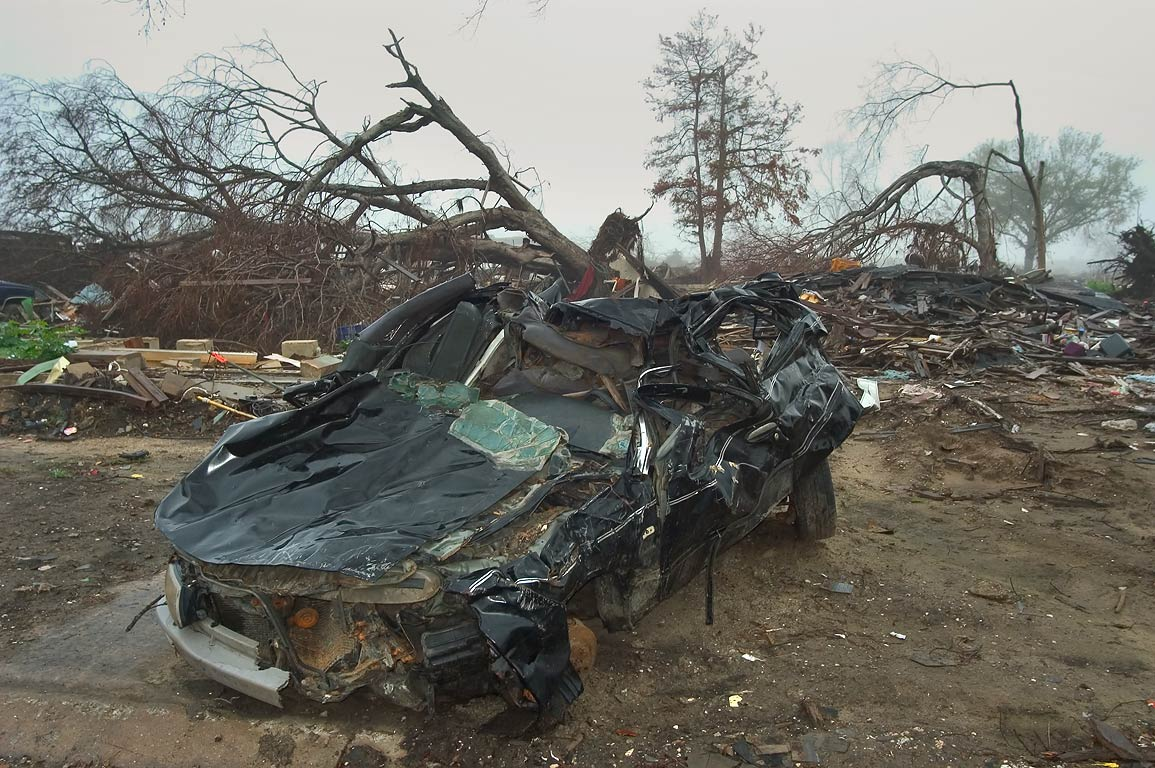 A damaged car and broken trees near Tennessee St...fog at morning. New Orleans, Louisiana