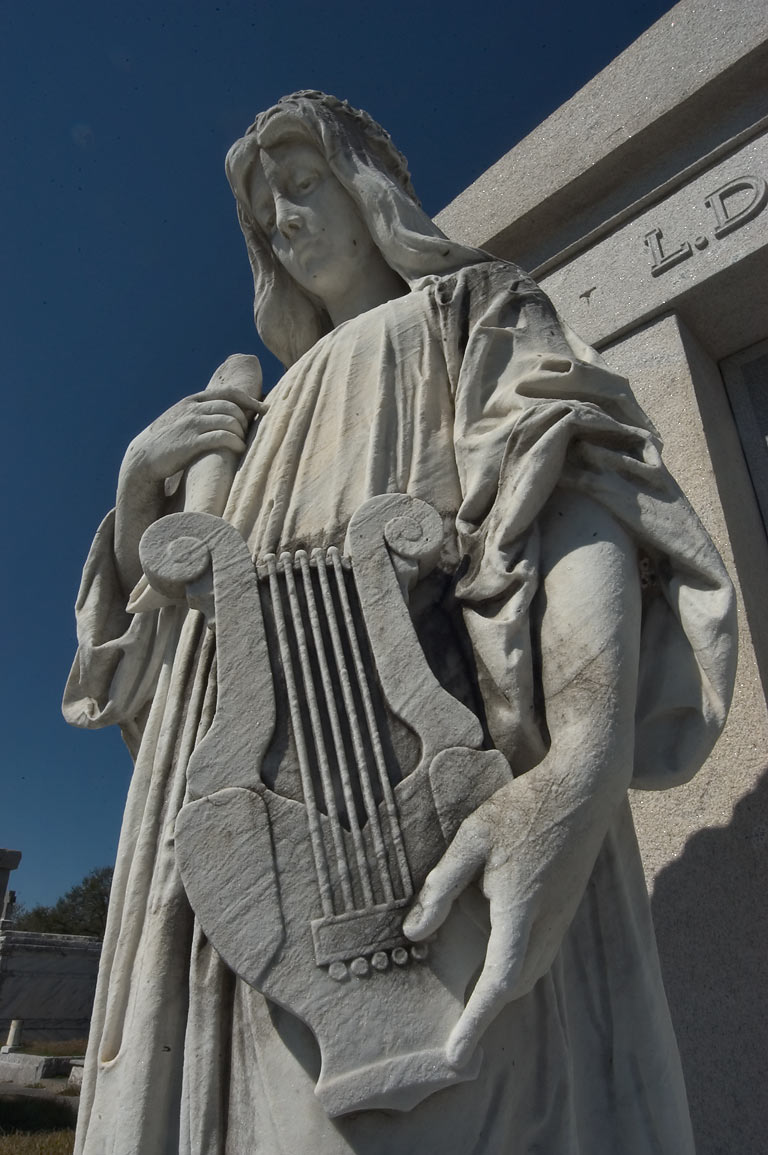 A marble harpist at a tomb of L. Denapolis in Metairie Cemetery. New Orleans, Louisiana
