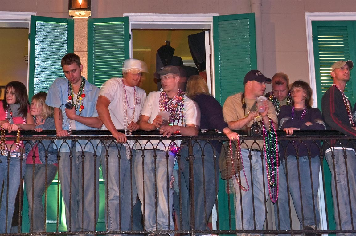 People on a balcony of a cafe celebrating Mardi...French Quarter. New Orleans, Louisiana