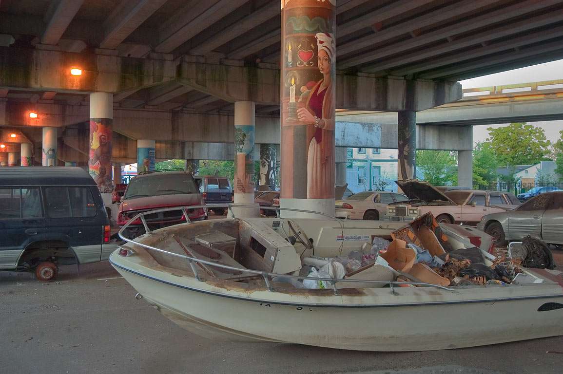 Abandoned boats and cars among pastel-painted...at evening. New Orleans, Louisiana