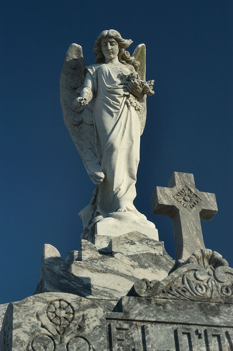 A sculpture of an angel on a tomb in White...Cemetery. New Orleans, Louisiana