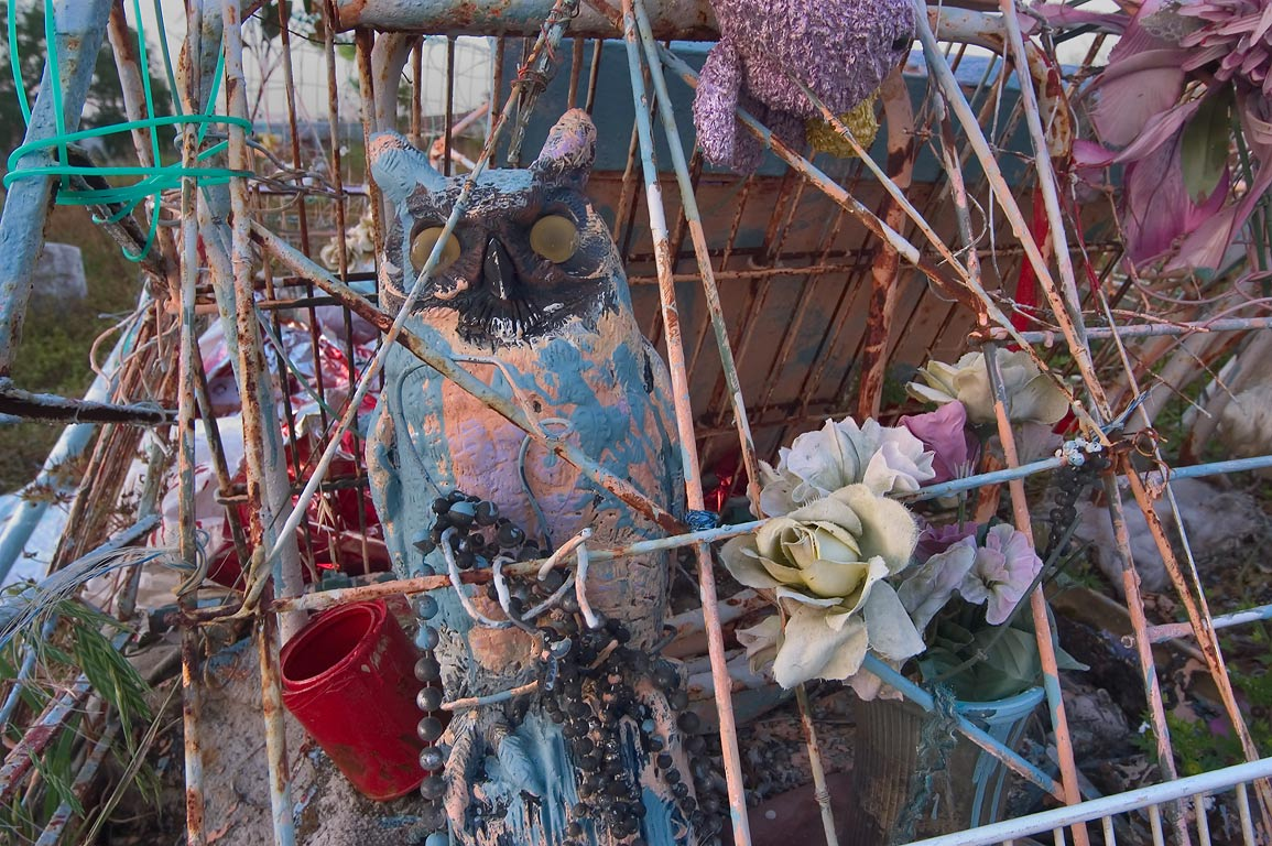 Assemblage of colorful ephemera on graveside art...Holt Cemetery. New Orleans, Louisiana