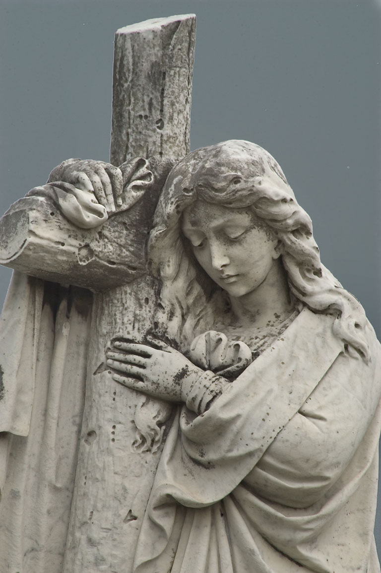 A woman hugging a cross on a tomb of Nevin-Ryan...Cemetery. New Orleans, Louisiana