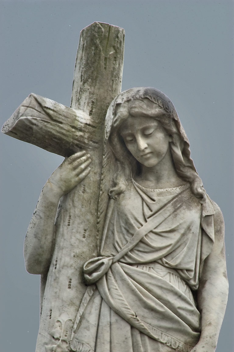 A woman holding a cross on a tomb in a corner of Metairie Cemetery. New Orleans, Louisiana