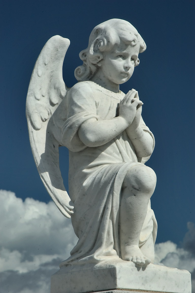 A young angel (cherub) sitting on a cloud in St...Cemetery No. 3. New Orleans, Louisiana