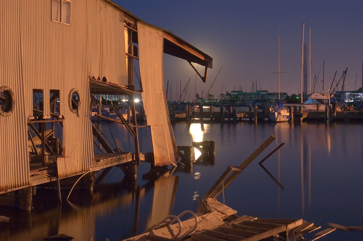 Ruins of boathouses and City Yacht Harbor in West End at moonrise. New Orleans, Louisiana