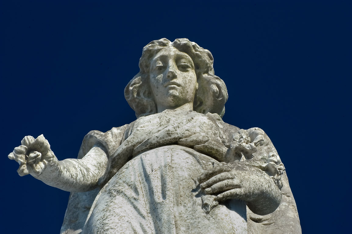 An angel with a flower atop of a tomb in Metairie Cemetery. New Orleans, Louisiana