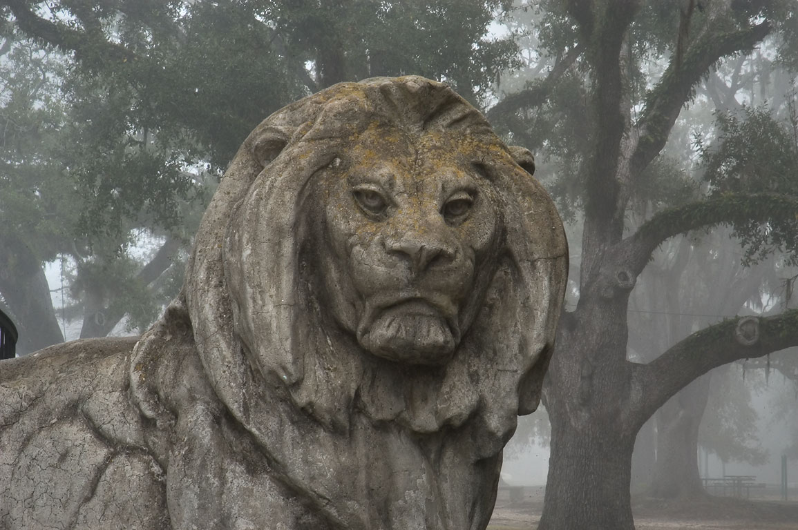 A concrete lion at Peristyle in City Park in fog. New Orleans, Louisiana