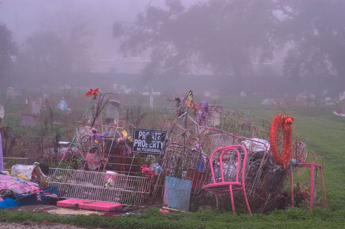 "A tomb decorated by ""folk art"" of an eccentric...in fog. New Orleans, Louisiana"