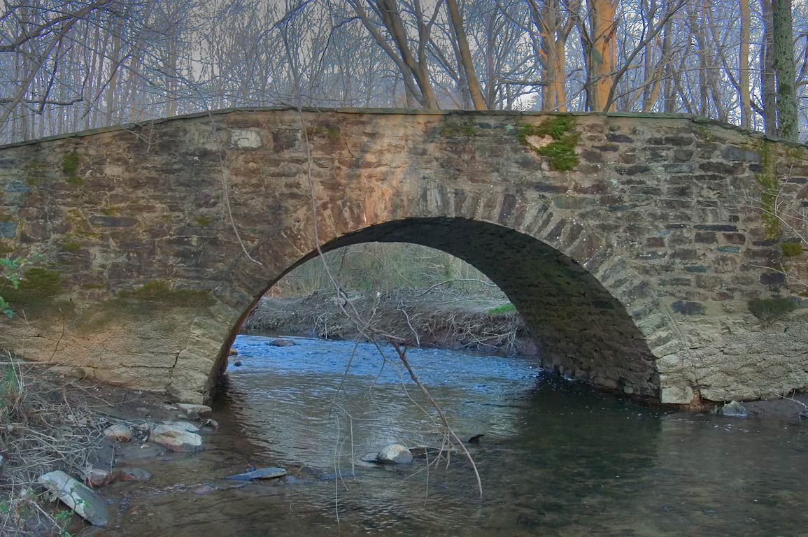 A stone bridge across Heathcote Brook in Cook Natural Area at sunset. Kingston, New Jersey