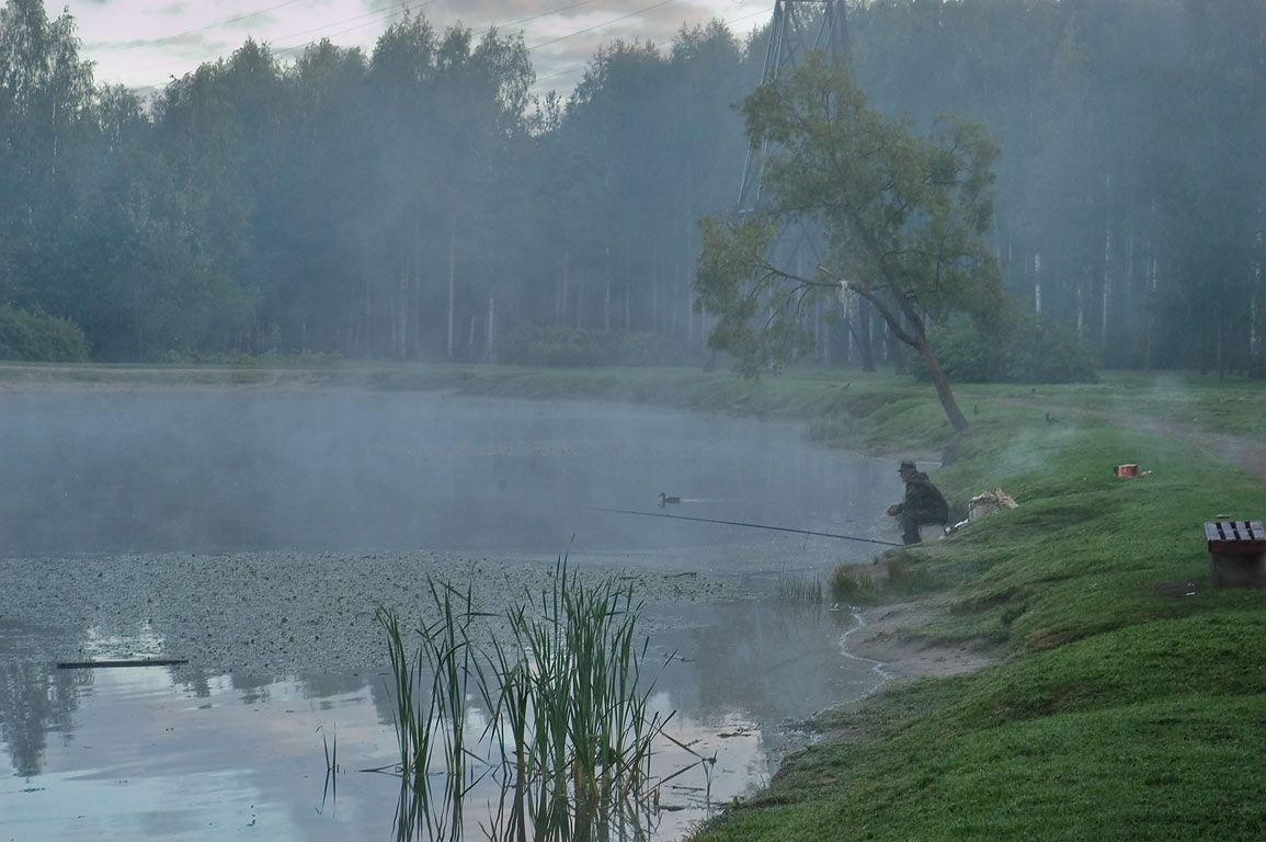 Fisherman on a lake in Sosnovka Park, near...at morning. St.Petersburg. Russia