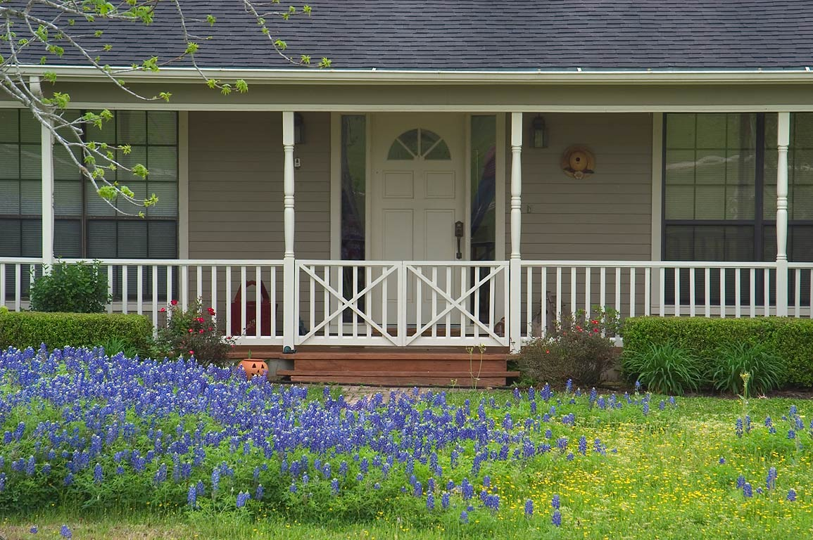House and bluebonnet at dead end of West Hilltop St.. East from Brenham, Texas