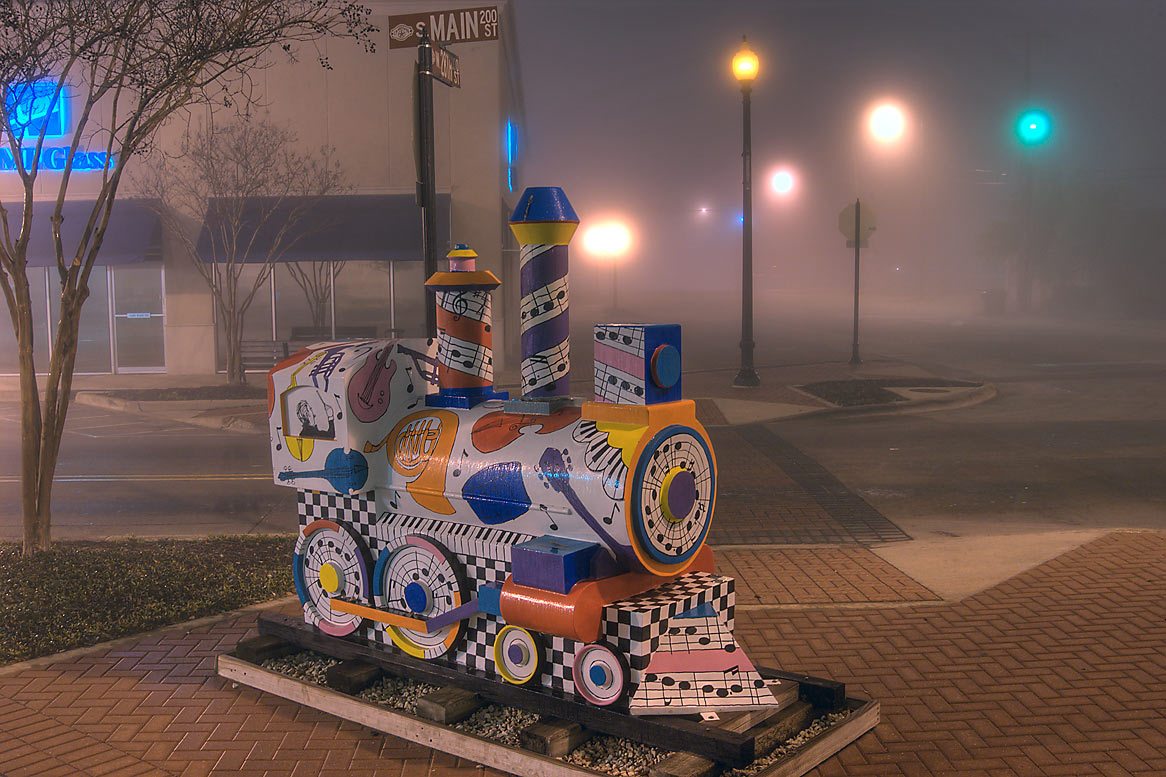 Wooden model of a train at crossing of South Main...in downtown, in fog. Bryan, Texas