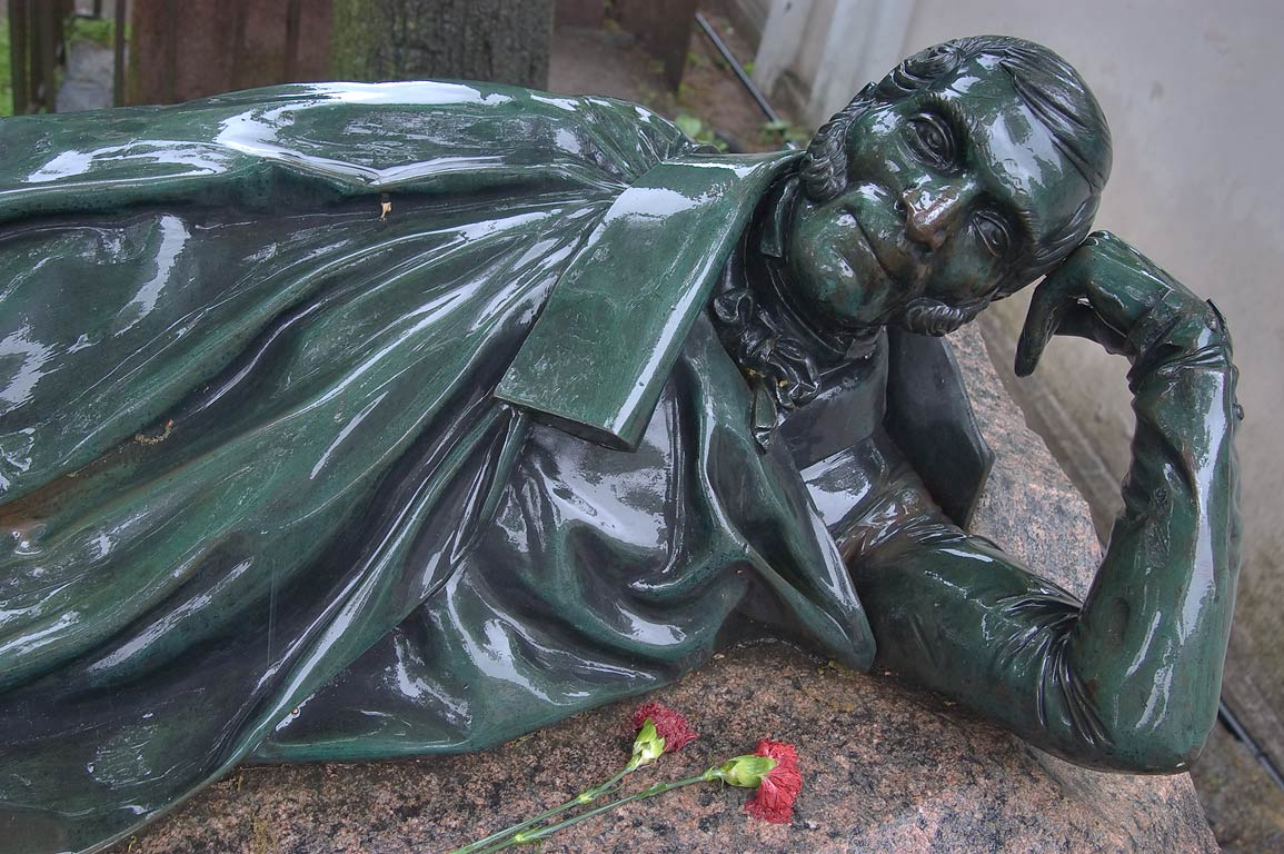 Bronze sculpture of a lying person on a tomb in...Cemetery). St.Petersburg, Russia