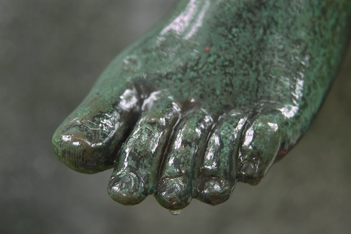 Bronze foot of a sculpture on a tomb in...Cemetery). St.Petersburg, Russia