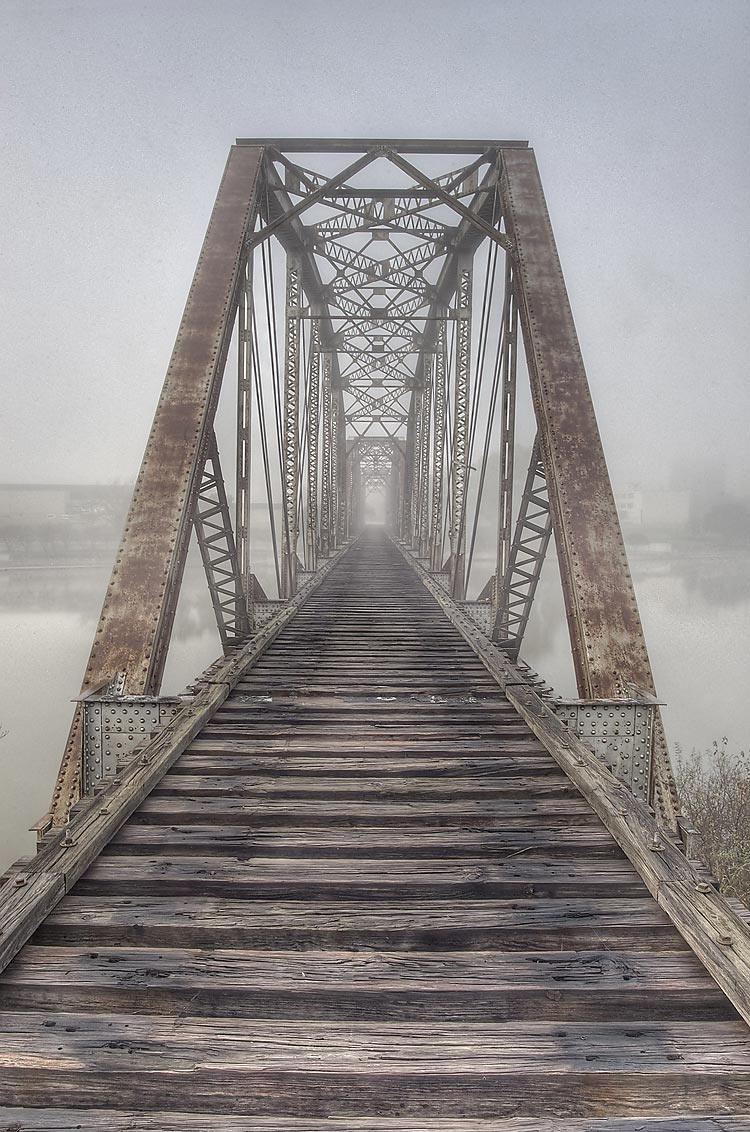 Railroad bridge in mist from north side of Brazos River. Waco, Texas