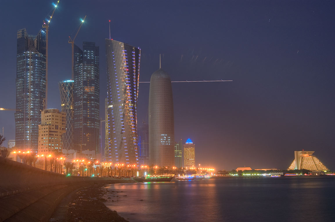 Corniche (seafront promenade) and area of West Bay at evening. Doha, Qatar