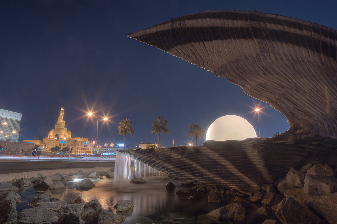 "Monstrous oyster with a pearl ""eating"" the city...mosque in background. Doha, Qatar"