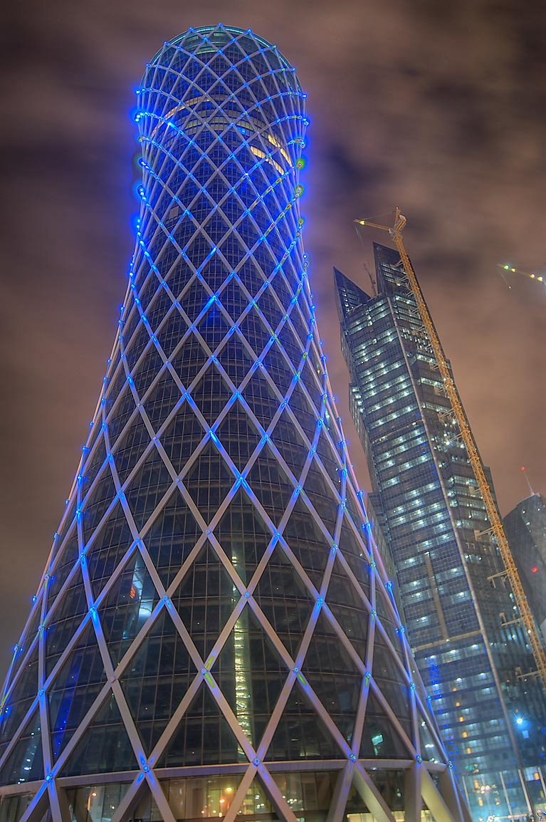 Tornado Tower (QIPCO Office) lighted in blue with some clouds at morning. Doha, Qatar