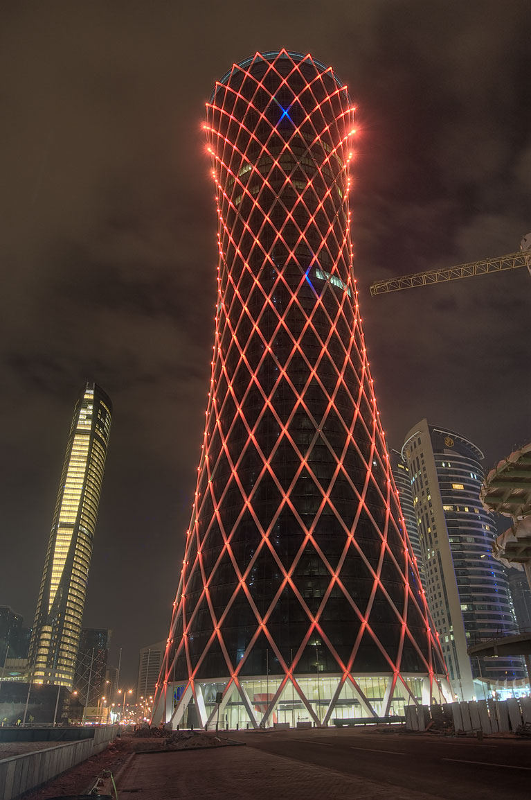 Tornado Tower (QIPCO Office) lighted in red at morning. Doha, Qatar