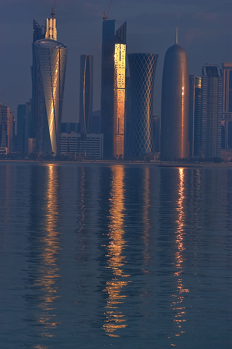 Reflections of West Bay towers in harbor from Corniche. Doha, Qatar