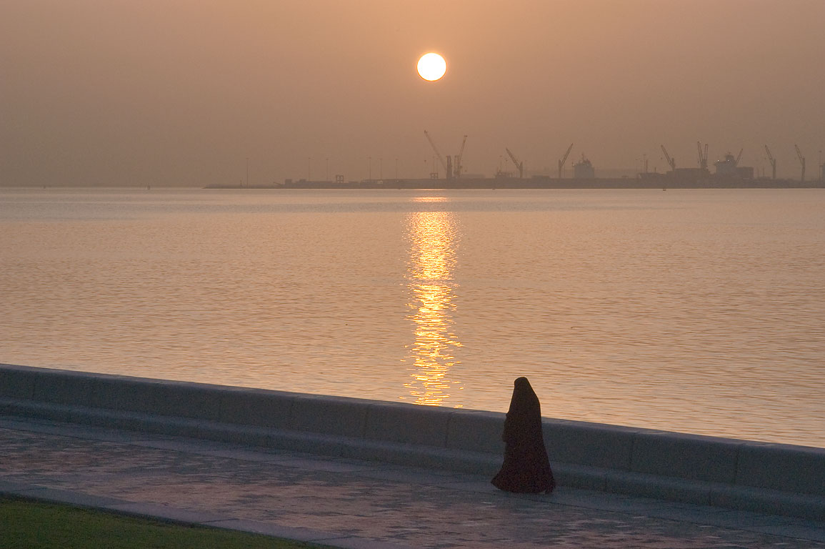 Woman in black gown jogging on Corniche (seafront promenade) at sunrise. Doha, Qatar