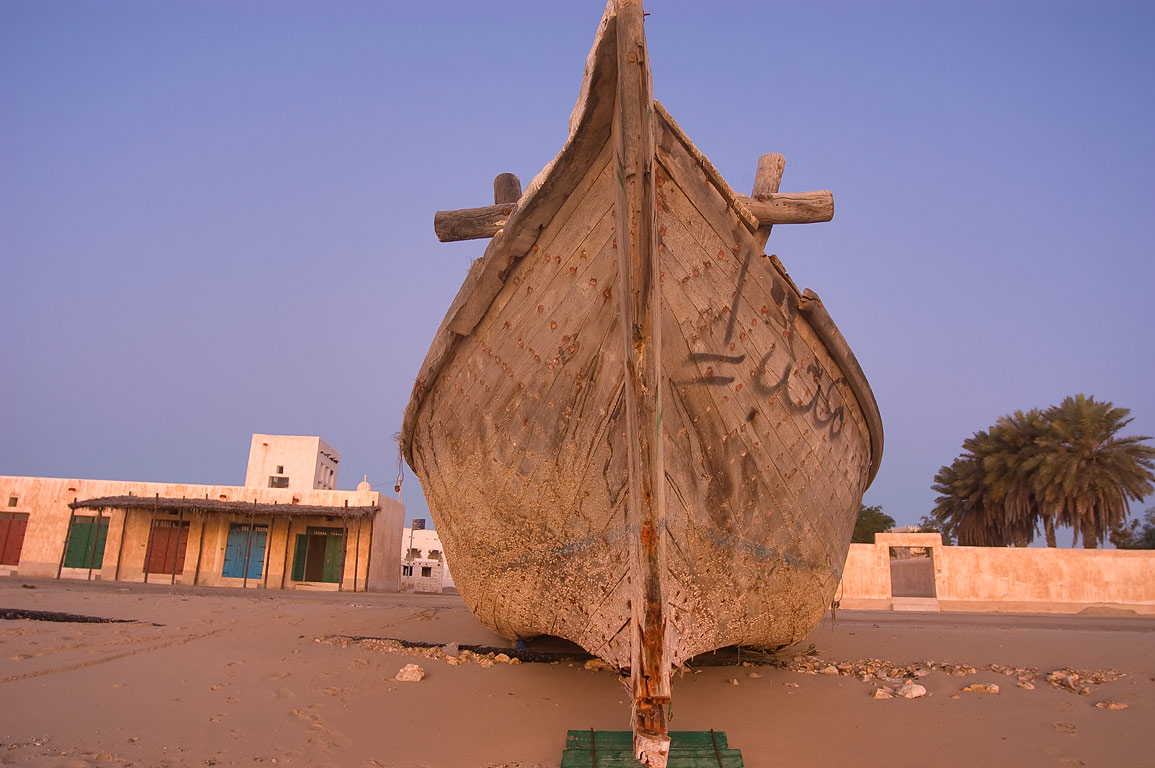Hull of beached dhow boat at sunrise in Al Wakra, south from Doha. Qatar