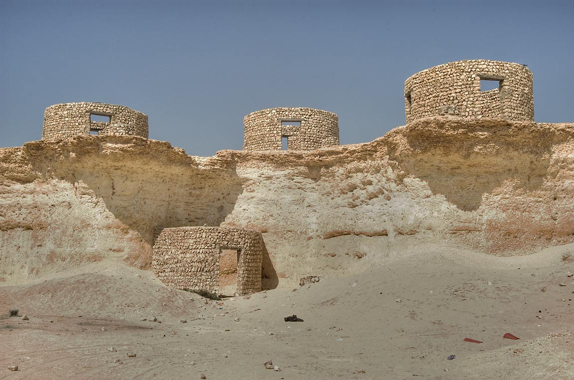 Stone huts nestling on limestone cliffs remained...area, north from Zekreet. Qatar