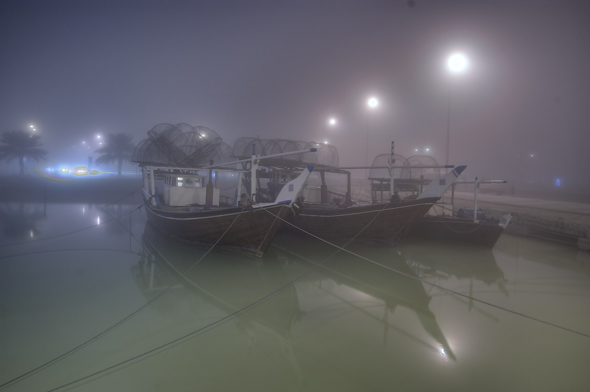 Dhow boats in a port at morning in fog. Doha, Qatar