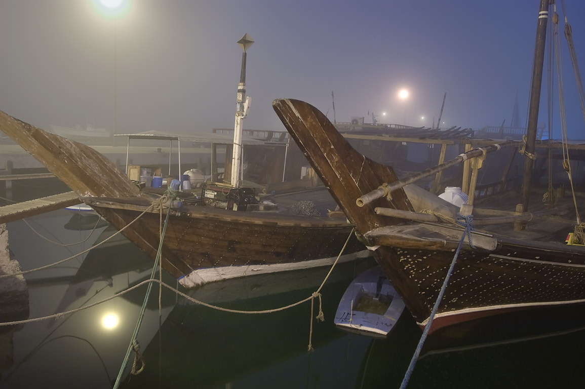 Dhow fishing boats in a port at morning in fog. Doha, Qatar