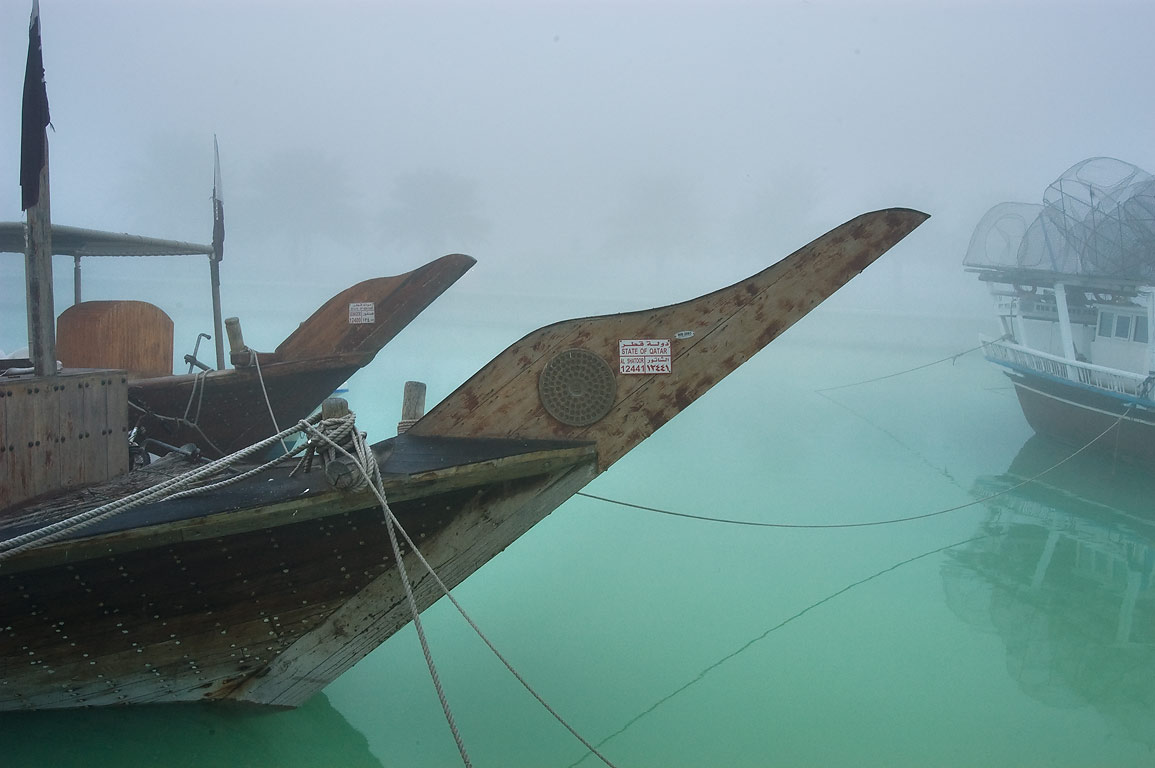 Dhow boats standing in a fishing port at morning in fog. Doha, Qatar