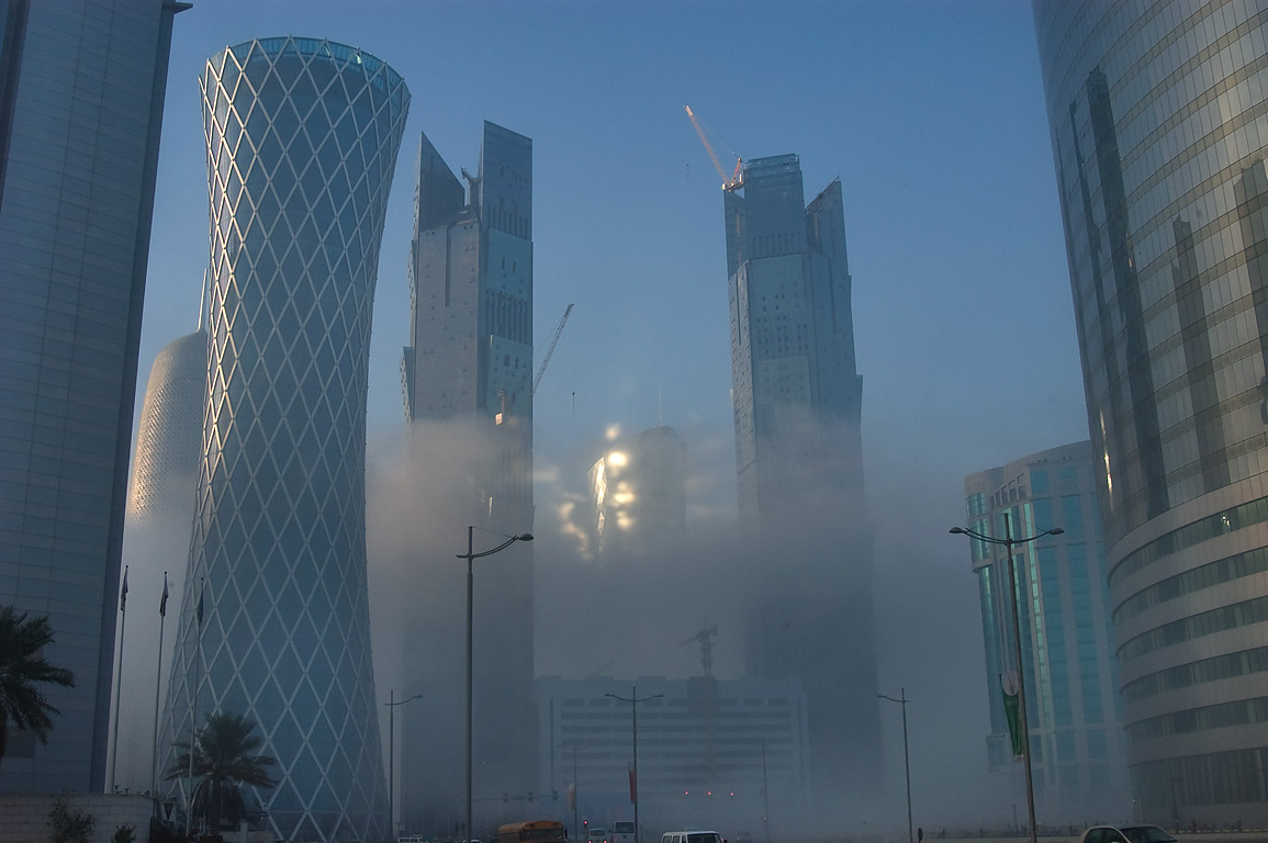 West Bay towers at sunrise in fog, view from Al Wahda St.. Doha, Qatar